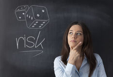 Businesswoman thinking of taking risks. Businesswoman thinking in front of a blackboard about to take risk or not. Risk written blackboard and dice shapes drawn Royalty Free Stock Images