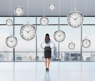 Businesswoman thinking about time, pocket watch hovering above. Businesswoman standing and looking into the window, back view, several models of pocket watches Royalty Free Stock Photography