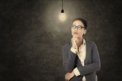 Businesswoman thinking under lit bulb Stock Photos