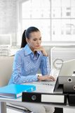 Businesswoman thinking at work. Using laptop computer at office desk Royalty Free Stock Photo