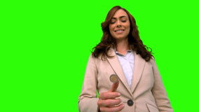 Businesswoman throwing a coin in the air on green screen stock video footage