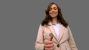 Businesswoman throwing a coin in the air on grey screen stock video