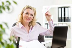 Businesswoman throwing paper airplane in office Stock Photos