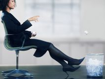 Businesswoman Throwing Paper Ball Into Dustbin royalty free stock photo
