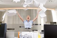 Businesswoman throwing paper up in office, arms raised, smiling, low angle view Stock Photography