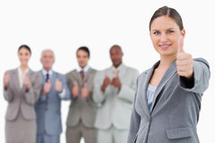 Businesswoman with thumb up and colleagues behind her Royalty Free Stock Photography