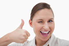 Businesswoman with the thumb up while winking Royalty Free Stock Photography