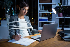 Businesswoman tied with rope while working on laptop at her desk Stock Photography