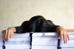 Businesswoman tired and sleep at pile of papers Royalty Free Stock Photography