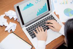 Businesswoman tired and stressed with overworked at desk. Girl with worried not idea with graph analysis laptop and crumpled paper at office, business concept Royalty Free Stock Photos