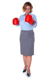 Businesswoman about to punch you. Businesswoman wearing boxing gloves about to throw a punch, isolated on a white background royalty free stock images