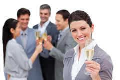 Businesswoman toasting with Champagne with team. Fortunate business team toasting with Champagne with team in the background Stock Images