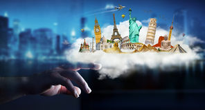 Businesswoman touching a cloud full of famous monuments with her. Businesswoman on blurred background touching a cloud full of famous monuments with her finger Stock Photo