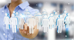 Businesswoman touching 3D rendering group of people with her fin. Businesswoman on blurred background touching 3D rendering group of people with her finger Stock Images