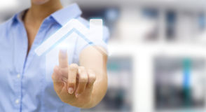 Businesswoman touching 3D rendering icon house with her finger. Businesswoman on blurred background touching 3D rendering icon house with her finger Stock Photo