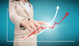 Businesswoman touching futuristic red and white graph with arrows. On blue background stock images