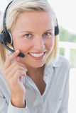 Businesswoman touching headset and smiling at camera Stock Photos