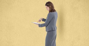 Businesswoman touching screen of tablet PC over beige background Stock Images