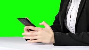 Businesswoman touching smartphone. Green screen stock footage