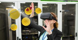Businesswoman touching various emojis seen through VR glasses in office Royalty Free Stock Photo