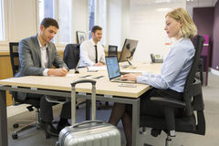 Businesswoman in transit with luggage in a coworking office stock photo