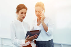 Businesswoman transmits information over mobile phone while partner holding touch pad in front of her, Royalty Free Stock Image