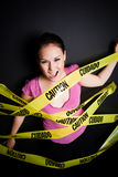 Businesswoman trapped in caution tape. A businesswoman trapped and caught in yellow caution tape stock photography