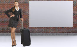 Businesswoman with travel bag against brick wall Stock Image
