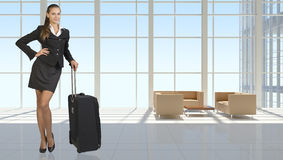 Businesswoman with travel bag in vast interior Royalty Free Stock Photography