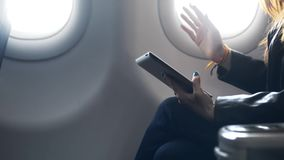 Businesswoman is travel on south sitting near window and talking with friend just at aircraft flight. stock video footage