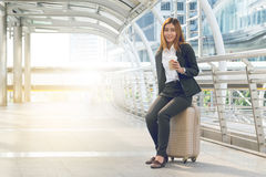 Businesswoman traveler with luggage at city background. Royalty Free Stock Photography