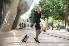 Businesswoman traveling with luggage and mobile phone Stock Image