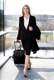 Businesswoman traveling, pulling suitcase along inside station or airport Royalty Free Stock Photography