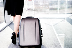 Businesswoman traveling, pulling suitcase along inside station or airport Stock Image