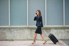 Businesswoman traveling with suitcase Stock Images