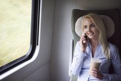 Businesswoman traveling by train. Smiling blonde businesswoman talking by mobilephone Stock Photo