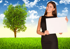 Businesswoman with tree and green landscape Royalty Free Stock Photo