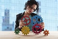 Businesswoman tries to connect gears pieces. Concept of Teamwork, partnership and integration stock images