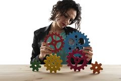 Businesswoman tries to connect gears pieces. Concept of Teamwork, partnership and integration royalty free stock photos