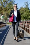 Businesswoman with trolley bag walking in urban environment. Wearing a red bag Royalty Free Stock Photo
