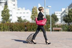 Businesswoman with trolley bag walking in urban environment. Wearing a red bag Stock Photo