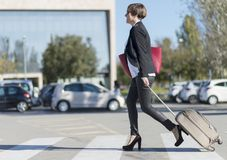 Businesswoman with trolley bag walking in urban environment. Wearing a red bag Royalty Free Stock Photography