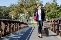 Businesswoman with trolley bag walking in urban environment. Wearing a red bag Stock Photography