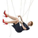 Businesswoman trying to break free while hanging on manipulating ropes. Isolated on white Stock Photos