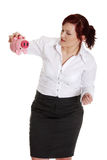 Businesswoman trying to get money from her piggy Stock Images