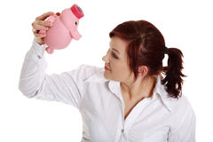 Businesswoman trying to get money from her piggy Royalty Free Stock Photography