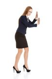 Businesswoman trying to push the wall Stock Photography