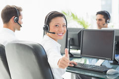Businesswoman with tumbs up looking at camera while her colleagues working Royalty Free Stock Images