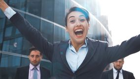 Businesswoman and two businessman rejoice and jump with happiness