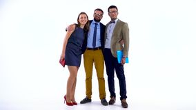 Group of three business partners posing in studio for camera. Slow motion. Businesswoman and two male coworkers posing for camera in studio. Slow motion stock footage